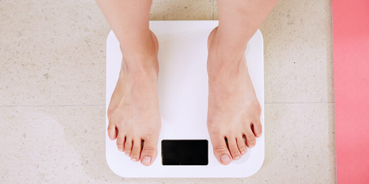 man weighing himself on a scale after ACV